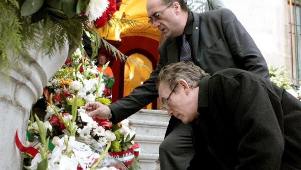 Dos personas depositan flores en la escalinata del Ayuntamiento de Bilbao