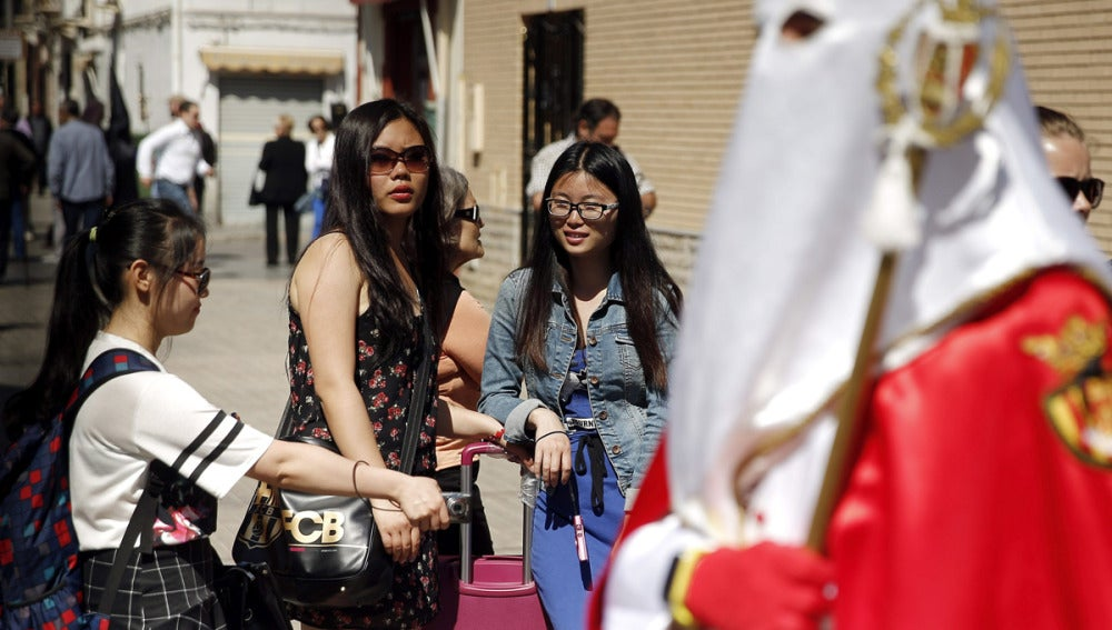 Turistas viendo un paso de Semana Santa
