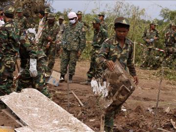 Soldados laosianos recuperan partes del fuselaje de un avión