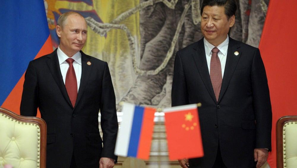 El presidente ruso, Vladímir Putin (i), y su homólogo chino, Xi Jinping, antes de firmar el acuerdo