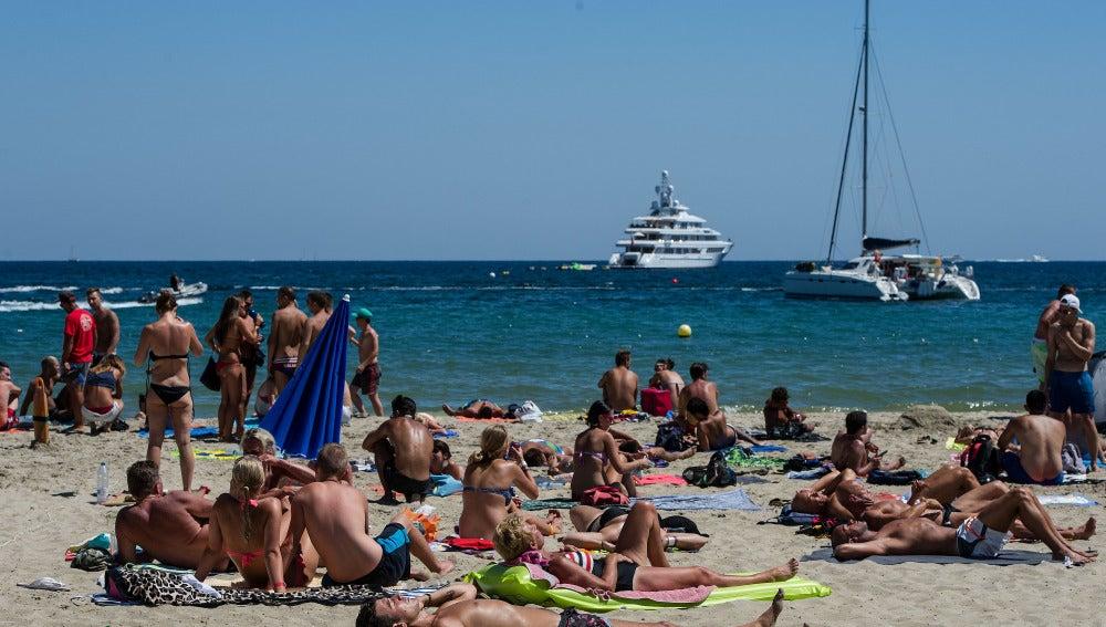 Playa de Ibiza llena de personas tomando el sol