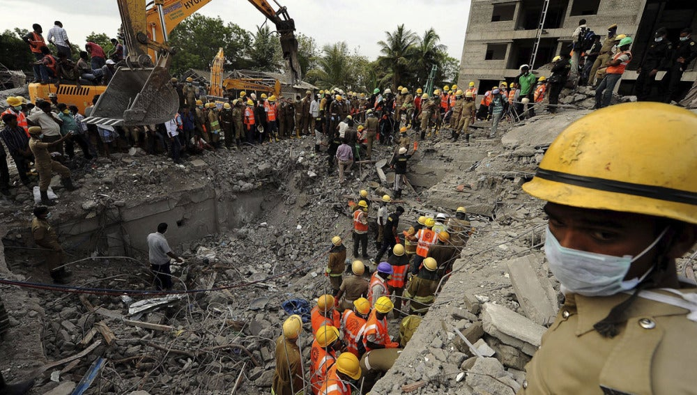 Miembros de los equipos de rescate buscan víctimas en el lugar del edificio derrumbado