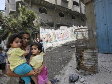 Un padre huye junto a sus hijos durante un bombardeo en Gaza