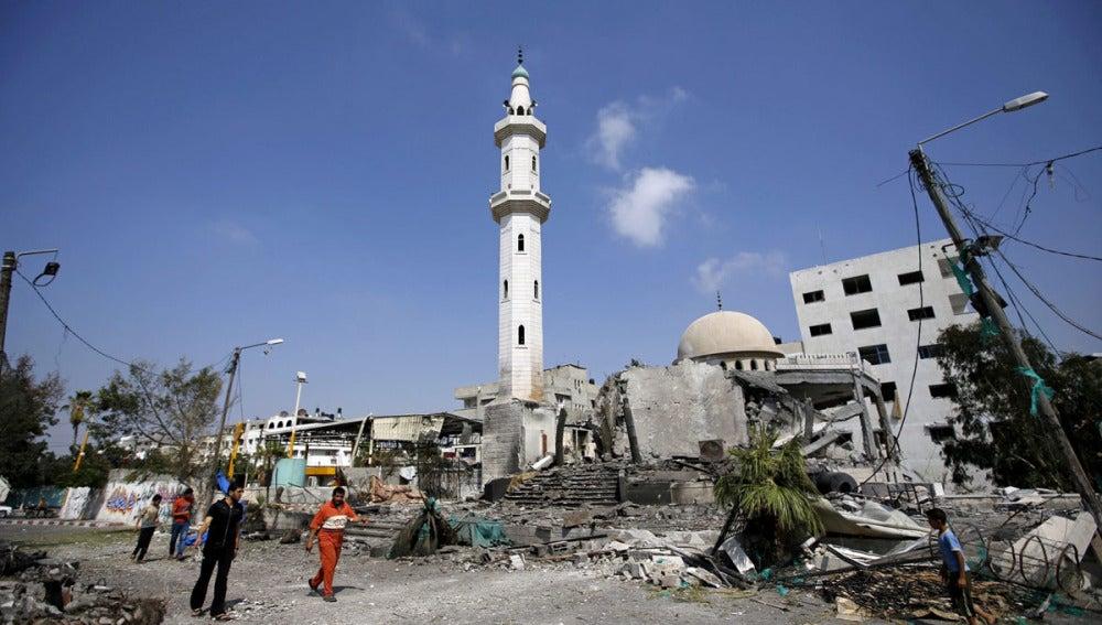 Palestinos caminando cerca de una mezquita