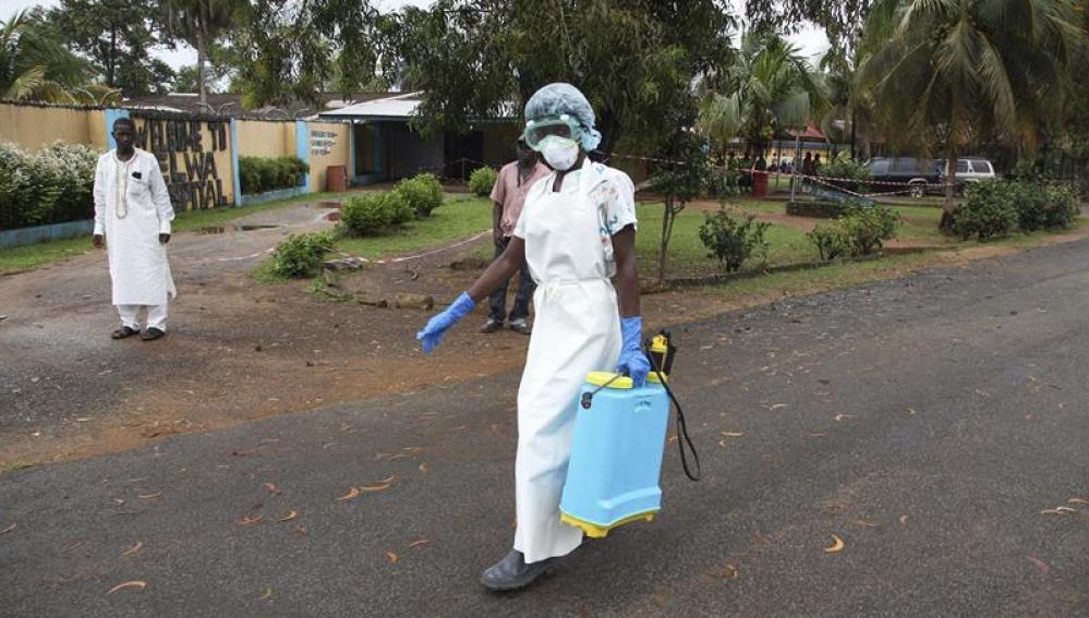 Una enfermera esparce desinfectante en las inmediaciones de un hospital