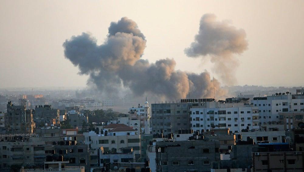 Una columna de humo se levanta por encima de los edificios en la ciudad de Gaza