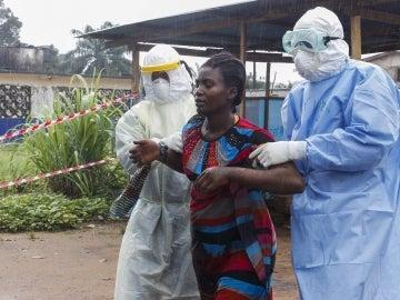 Unos enfermeros escoltan a una mujer supuestamente enferma del ébola