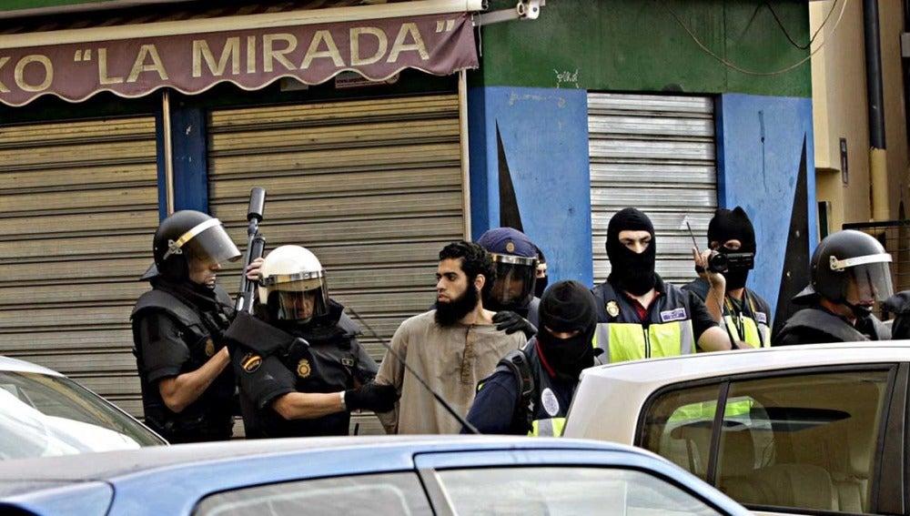 Agentes de policía junto a uno de los detenidos