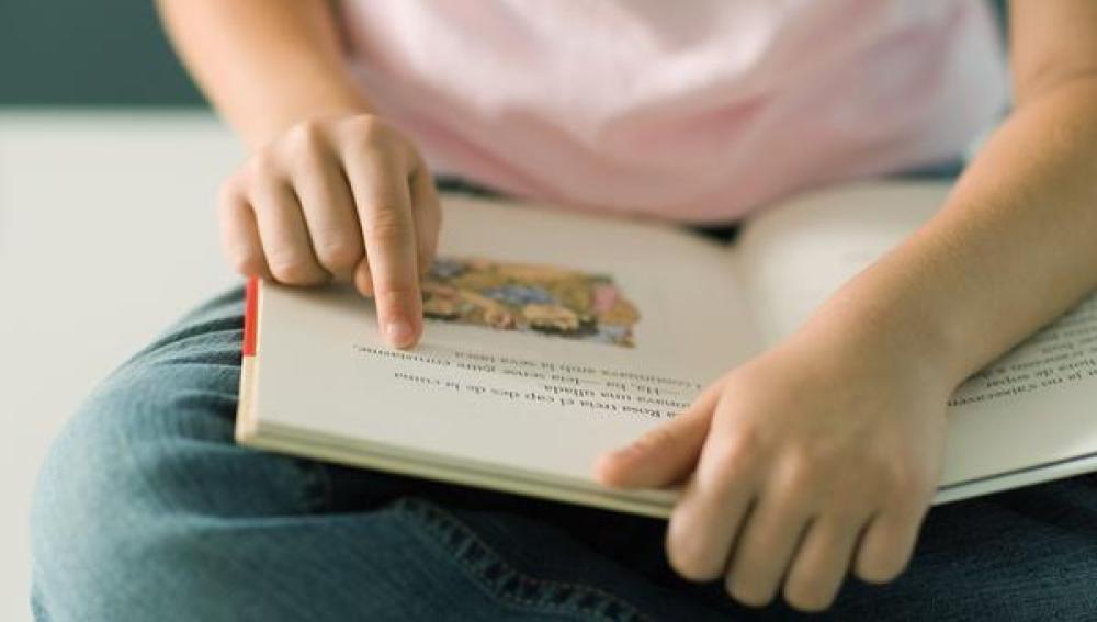 Una niña lee un libro de texto.