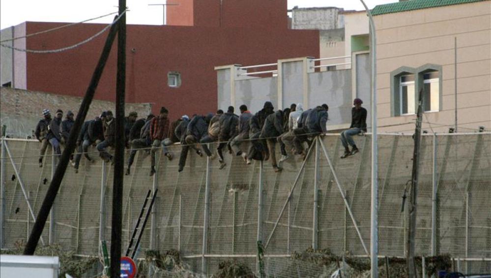 Imagen de unos inmigrantes encaramados en la valla de Melilla el pasado mes de diciembre.