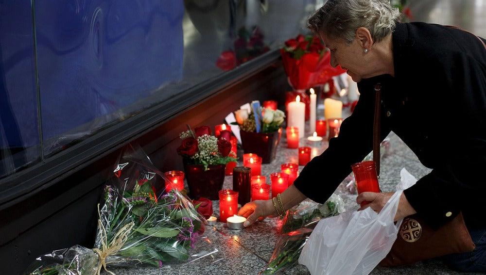 Una mujer enciende una vela en el monumento a las víctimas en Atocha