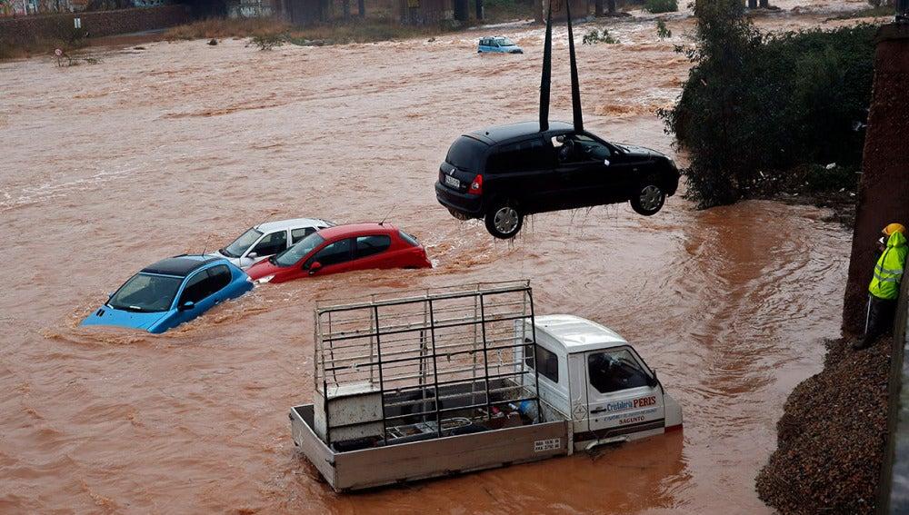 Varios coches arrastrados por el río Palancia a su paso por Sagunto