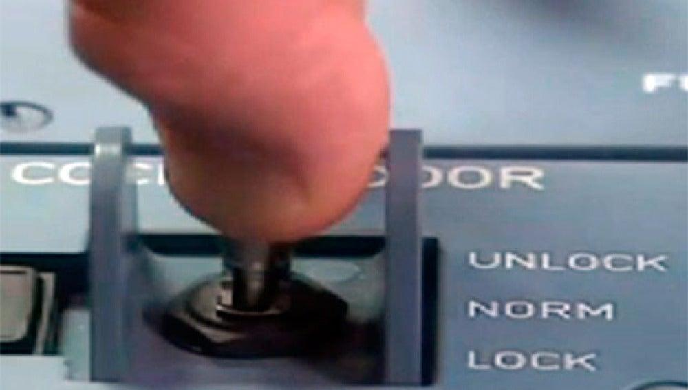Botón que impide la apertura de la puerta de cabina de un avión
