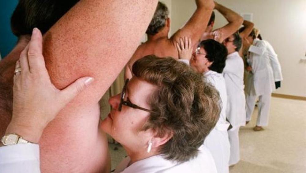 Mujeres oliendo sobacos durante un experimento