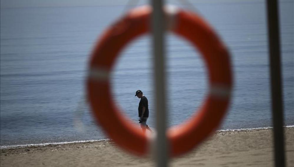 Un turista pasea por la orilla del mar en una playa.