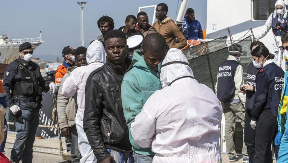 Un grupo de inmigrantes rescatado por un barco RBD desembarca al puerto de Corigliano Calabro (Italia)