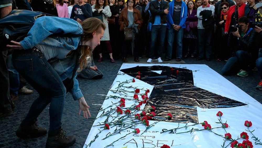 Una joven deposita flores en el homenaje al profesor fallecido