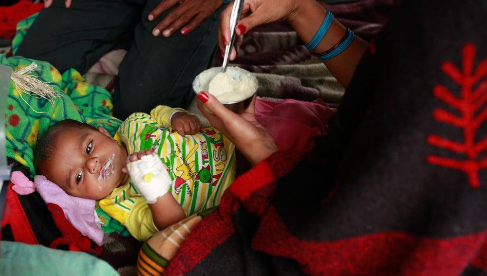 Un bebé es alimentado por su madre en un campamento de afectados en Nepal.