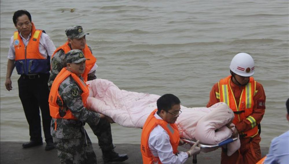Miembros de los servicios de rescate trasladan a un superviviente del naufragio