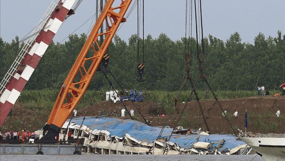 Una grúa saca del agua el barco naufragado en el río Yangtsé