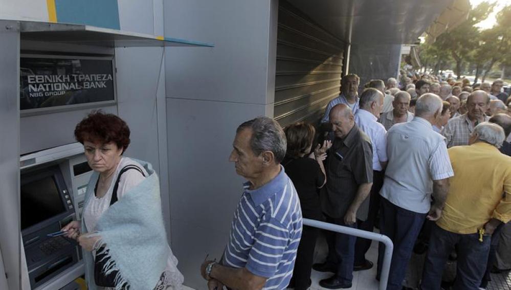 Jubilados sacan dinero de un cajero en Grecia.