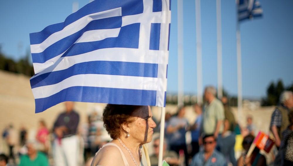 Una mujer porta una bandera de Grecia