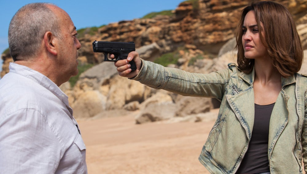 María apunta a Enrique con una pistola