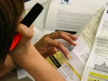Una mujer estudia su factura de la luz