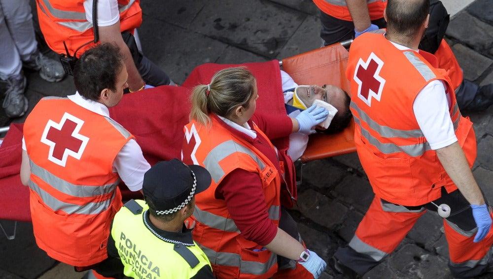 Un mozo es trasladado por los servicios médicos tras resultar herido en el último encierro de los Sanfermines