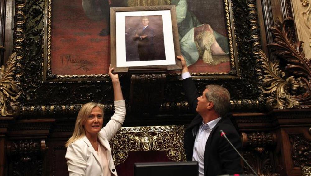 Los concejales del PPC Alberto Fernández Díaz y Ángeles Esteller colocan una fotografía de Felipe VI