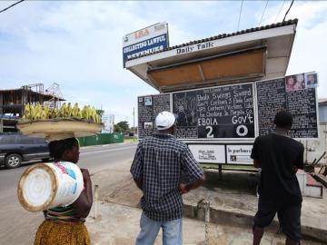 Varias personas leen unas instrucciones sobre el Ébola