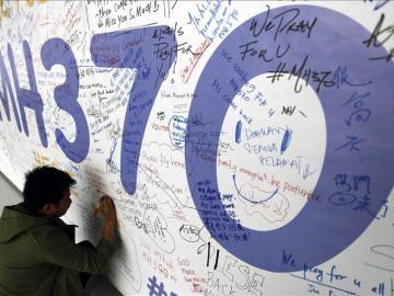 Un hombre escribiendo mensajes en honor a las víctimas del vuelo MH370 de Malaysia Airlines