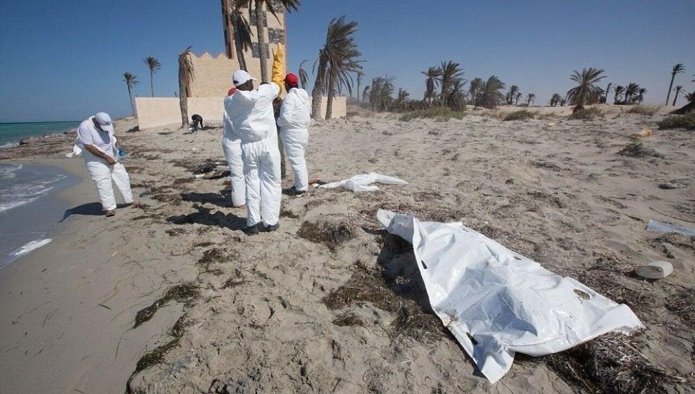 Voluntarios de la Media Luna Roja recogiendo los restos de un inmigrante en Libia