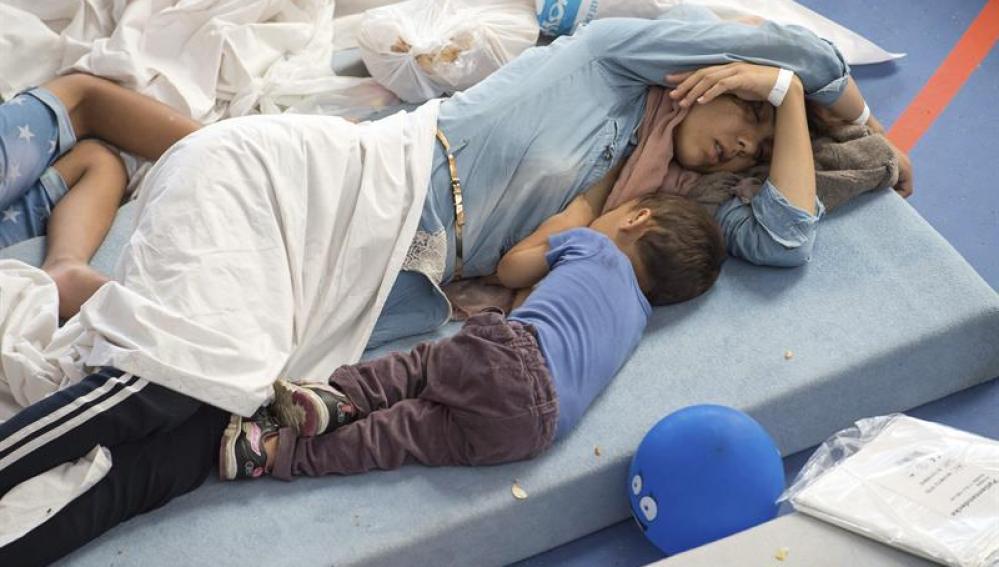Varias personas descansan en un centro para refugiados de Deggendorf, Alemania