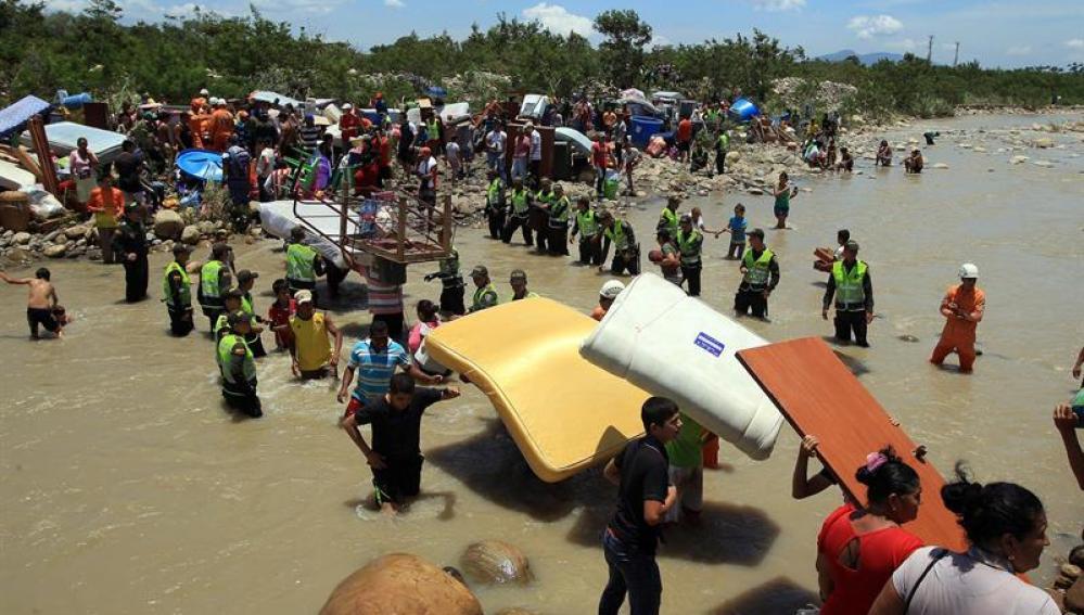Cientos de colombianos cargan sus pertenencias por el río Táchira