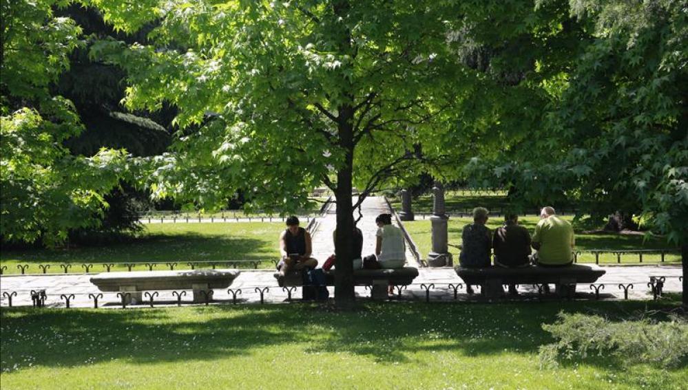 Varias personas decansan en los bancos del Paseo del Prado de Madrid