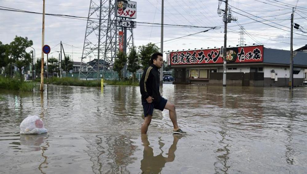 Un joven se abre paso entre las calles abnegadas por el agua en Japón.