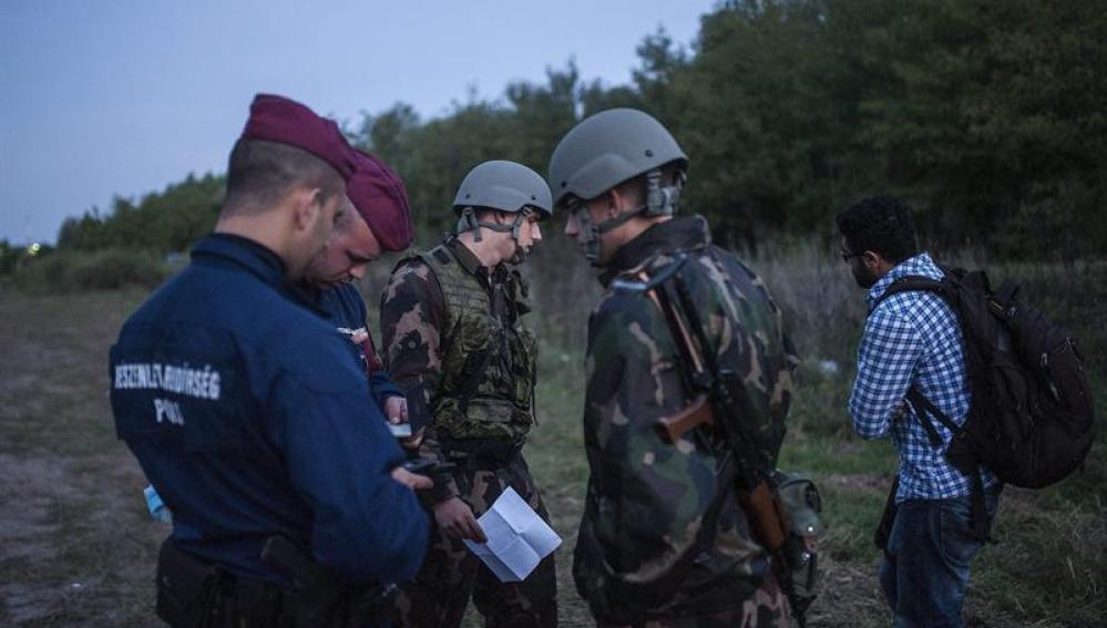 Policías y soldados comprueban la documentación de un refugiado en la frontera entre Serbia y Hungría.
