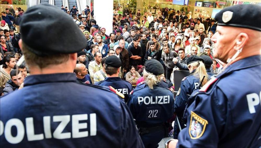 Policías frente a los cientos de refugiados que esperan la llegada de más trenes con dirección a Alemania.