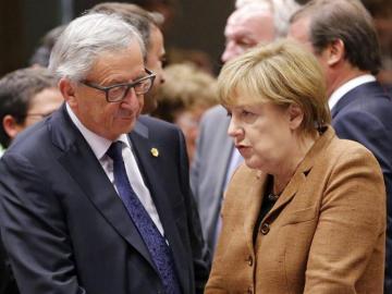 El presidente de la Comisión Europea, Jean Claude Juncker, conversa con la canciller alemena, Angela Merkel