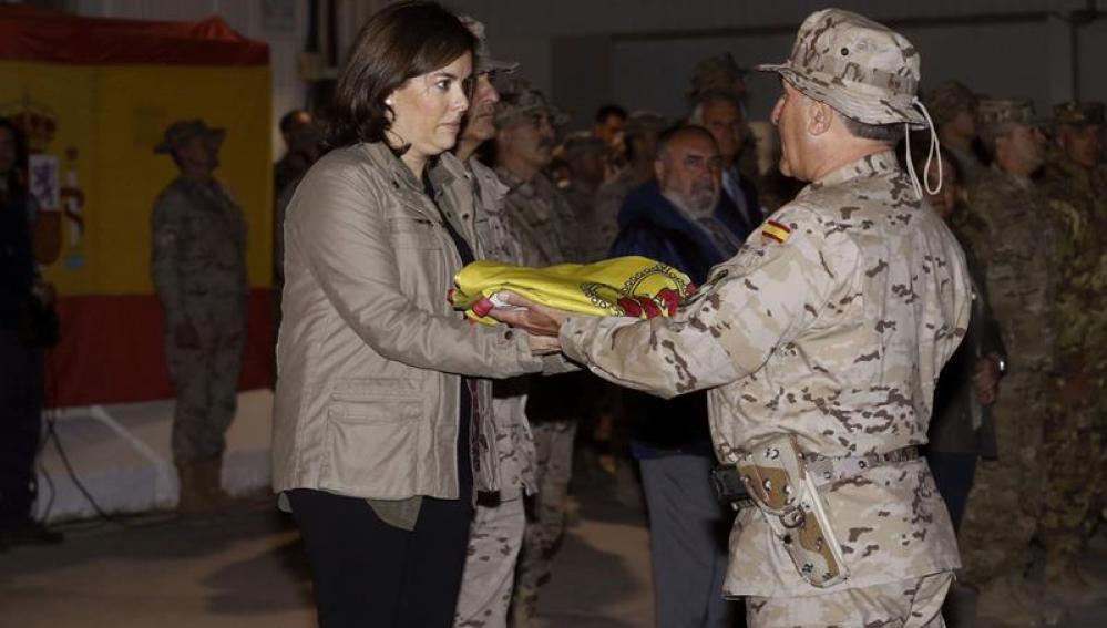 La vicepresidenta del Gobierno, Soraya Sáenz de Santamaría, recibe la bandera de manos del jefe del contingente español
