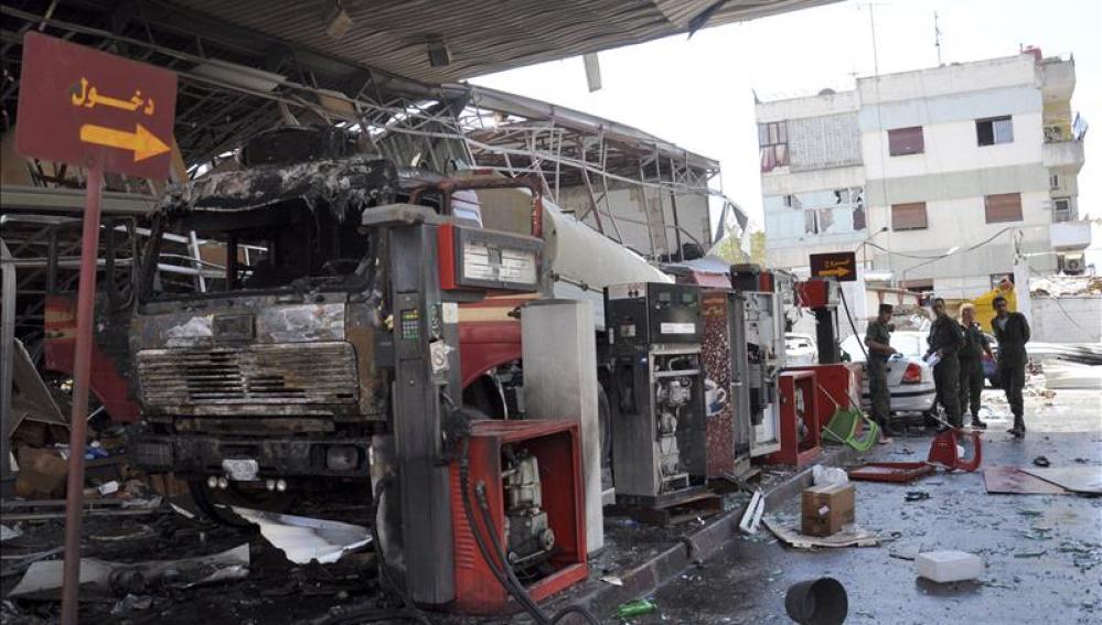 Soldados sirios inspeccionan los daños ocasionados por una granada de mortero
