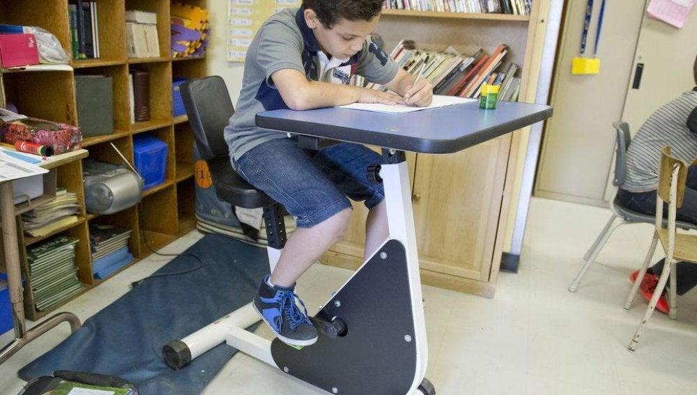 Imagen de un niño en el 'pupitre-bici'.