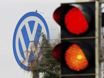 Logotipo de Volkswagen junto a un semáforo en rojo y naranja en Fallersleben, Alemania.