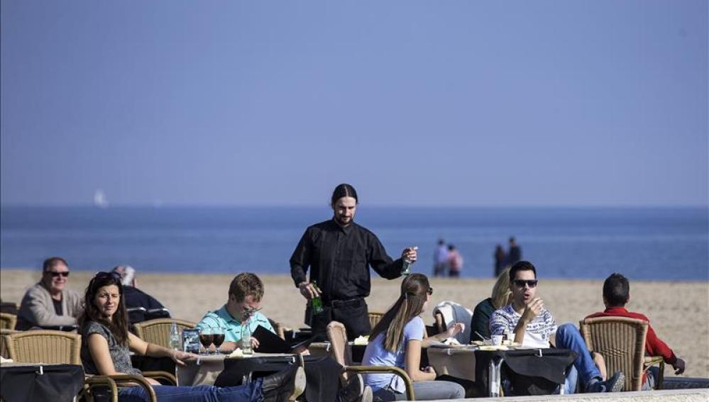 Varias personas disfrutan de las temperaturas suaves tomando un aperitivo en una terraza