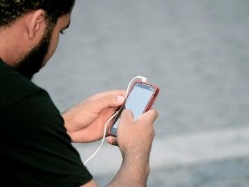 Un usuario mira su teléfono móvil