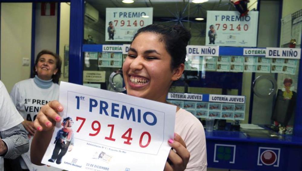 Una joven sonríe con una copia del número 79.140