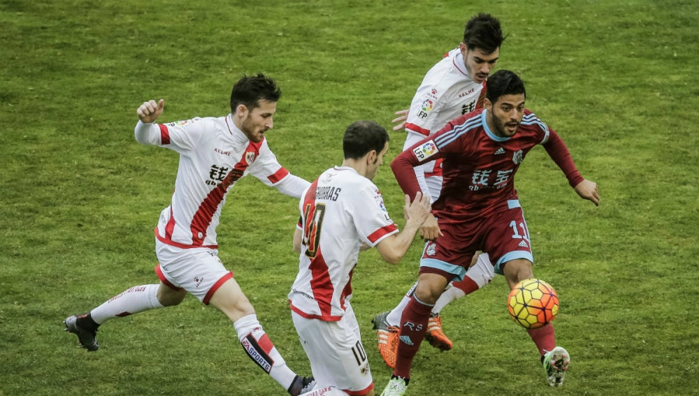 Carlos Vela conduce el balón ante la defensa del Rayo Vallecano