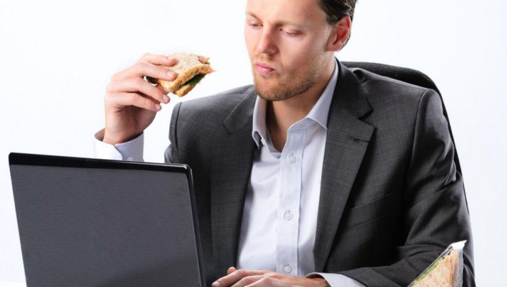 Un hombre comiendo un bocadillo en el trabajo