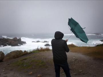 Un hombre ve cómo el viento le dobla el paraguas en A Coruña